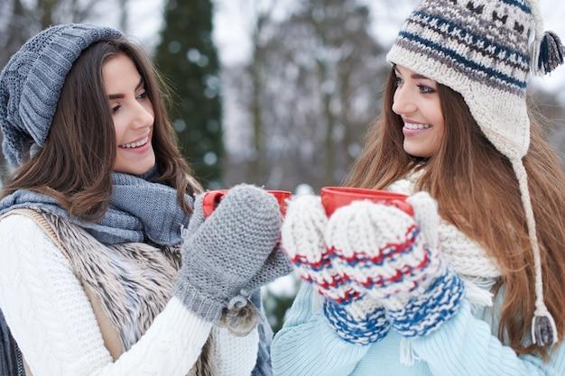Giovani amici con bevanda calda in inverno
