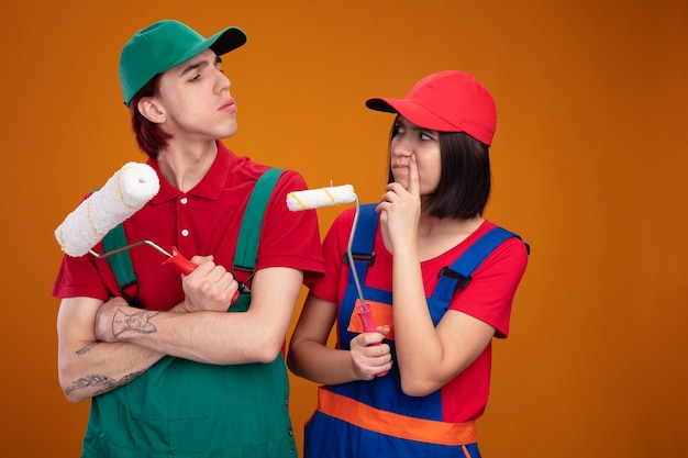 Young frowning couple in construction worker uniform and cap looking at each other holding paint roller guy standing with closed posture girl touching face with finger isolated on orange wall