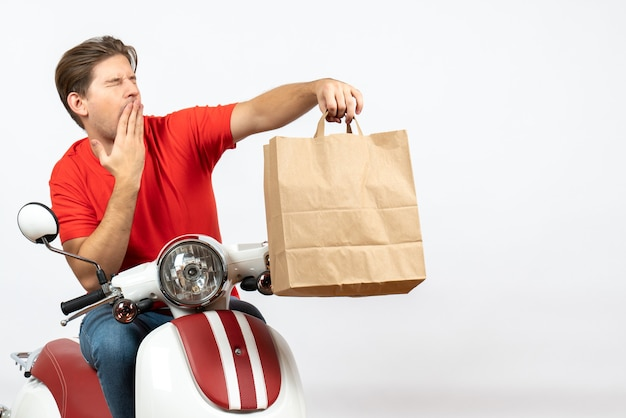 Young frowning courier guy in red uniform sitting on scooter giving paper bag on white wall