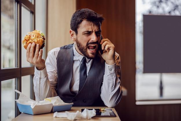 ファーストフードのレストランに座って、昼休みを食べて、従業員と不快な電話で話している不満の若いビジネスマン