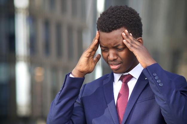 Молодой разочарованный отчаявшийся несчастный бизнесмен страдает головной болью, мигренью. черный афроамериканец афроамериканец в строгом костюме касается его головы, висков из-за боли. отчаяние, неудача