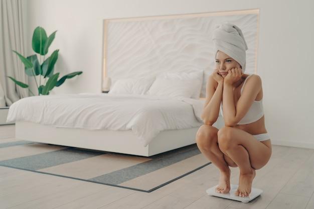 Молодая разочарованная женщина босиком в нижнем белье приседает на электронных умных весах во время утреннего взвешивания после душа, чтобы узнать свой результат. концепция здорового образа жизни и диеты