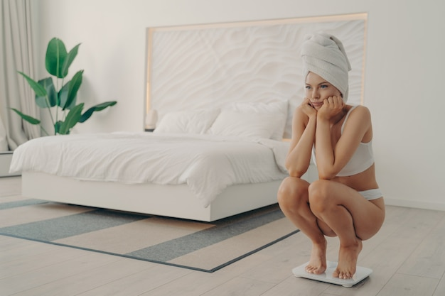 Young frustrated female barefoot in underwear squatting on electronic smart scales during morning weighing after shower procedure to find out her result. healthy lifestyle and dieting concept