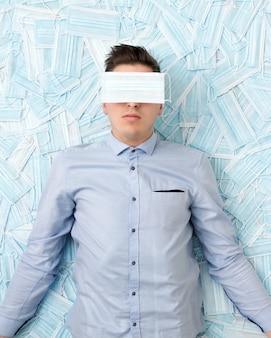 Молодой разочарованный парень с маской на лице лежит на разбросанных масках. понятие стресса во время пандемии и кризиса в мире.