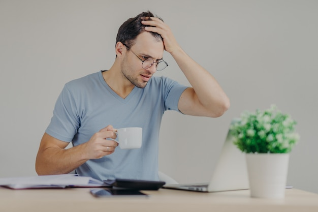 Young frustrated male does paperwork, reads with puzzled expression unpleasant information on laptop computer