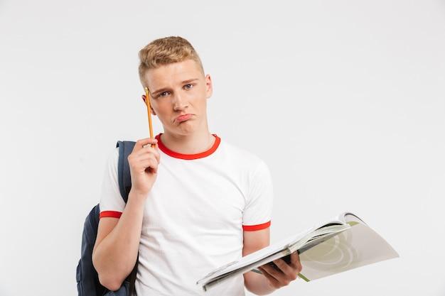 Молодой расстроенный студент мужского пола, носящий рюкзак, думая, изучая с учебниками и ручкой в руках, изолированных на белом