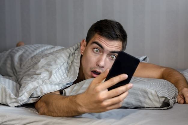 Young frustrated and stressed man is late. he is waking up, looking at smartphone and is shocked.