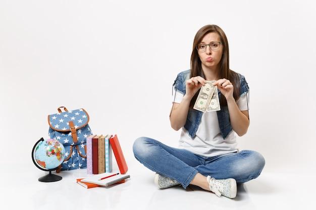 Молодая разочарованная студентка в очках, держащая долларовые купюры, имеет проблемы с деньгами, сидит рядом с земным шаром, рюкзаком, изолированными школьными учебниками