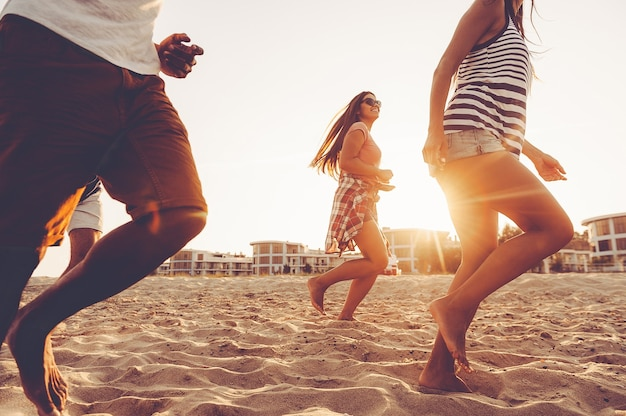 Young and full of energy. group of young cheerful people running along the beach and looking happy