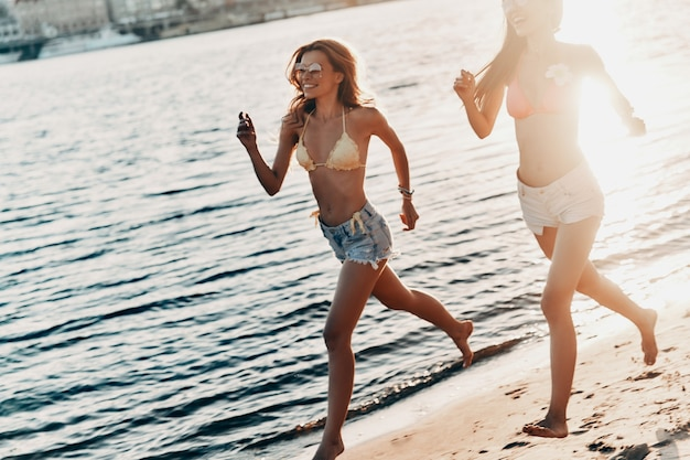 Young and full of energy. two attractive young women in swimwear smiling while running on the beach