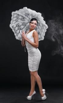 회색 배경에 흰색 드레스에 흰색 우산을 가진 젊은 전체 길이 여자
