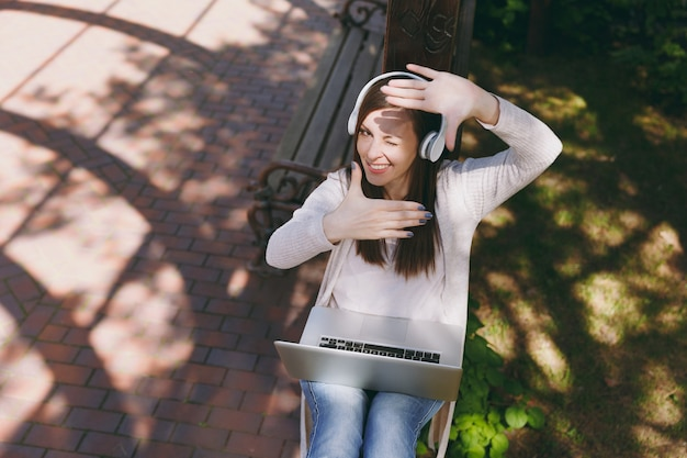 Young fun businesswoman making hands photo frame gesture. woman working on modern laptop pc computer, listen music in headphones on head in street outdoors. mobile office. freelance business concept.