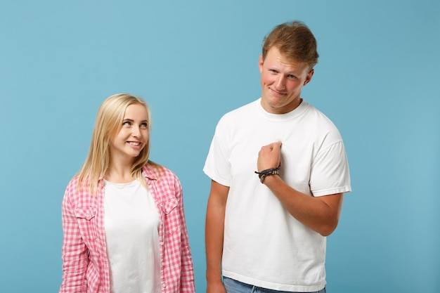 Young fun couple two friends guy girl in white pink empty blank design t-shirts posing