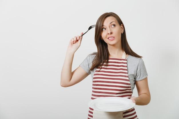 Молодая веселая сумасшедшая брюнетка-домохозяйка в полосатом фартуке серая футболка изолирована домработница, держащая белую пустую тарелку вилкой в волосах, как расческа для волос
