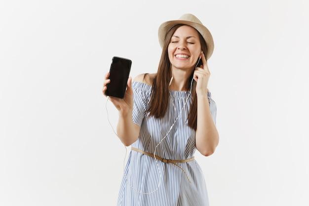 Молодая веселая счастливая женщина слушает музыку в наушниках на мобильном телефоне с пустым черным пустым экраном, изолированным на белом фоне. люди, искренние эмоции, концепция образа жизни. рекламная площадка. копировать пространство
