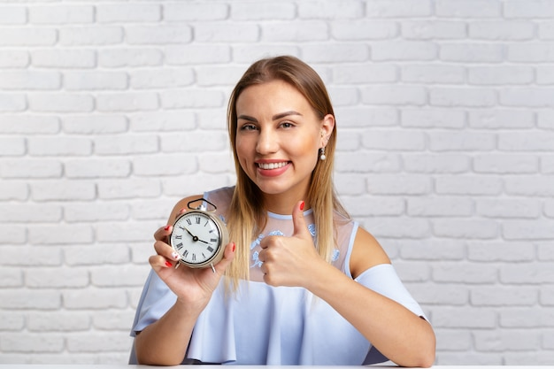 Young fun woman with alarm clock