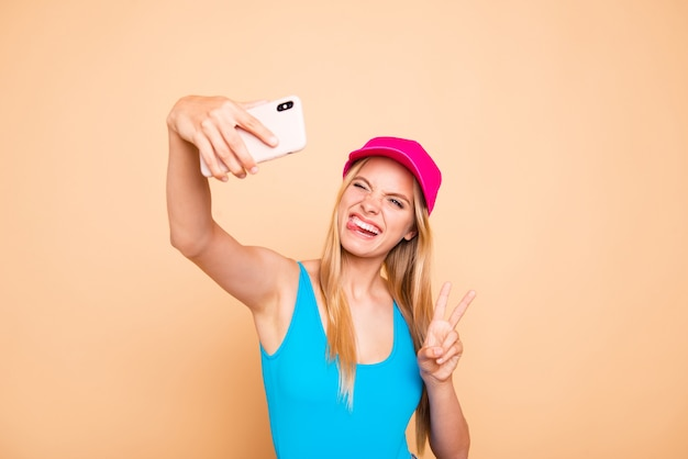 Young funky girl showing v-sign tongue out making self picture with smart phone