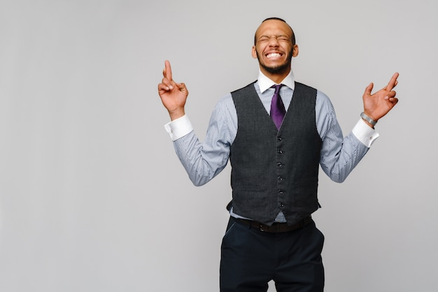 Young funny african-american businessman crossing fingers, wishing, hoping for best, miracle over grey.