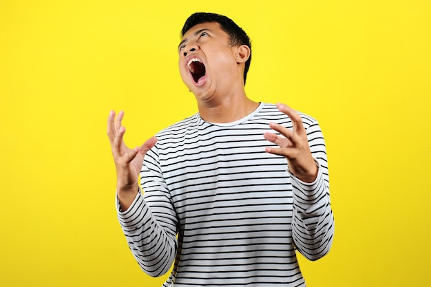 Young funny asian man doing angry gesture, annoyed, and emotional, isolated on yellow background