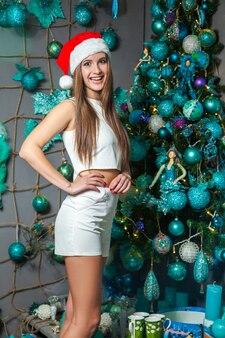 어두운 눈, 갈색 머리, 그리고 집에서 새해를 축하하는 산타 모자를 가진 젊고 재미있는 아름다운 패션 모델. 포즈를 취하고 카메라를 바라보는 긍정적인 감정이 있는 새해 장식. 밝은 파란색 장식.