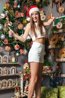 어두운 눈 갈색 머리와 새해를 축하하는 산타 모자와 젊은 재미 아름다운 패션 모델