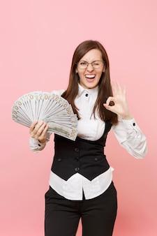 안경을 깜박이는 젊고 재미있는 비즈니스 여성은 많은 달러를 묶고 분홍색 배경에 격리된 확인 표시를 보여주는 현금 돈을 들고 있습니다. 여사장님. 성취 경력 부입니다. 광고 공간을 복사합니다.