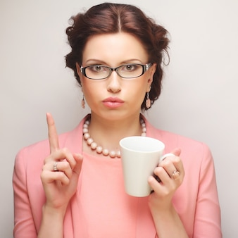 Young funny businesswoman having a coffee-break