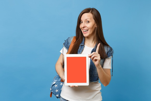 Young funny cheerful woman student pointing index finger up, holding tablet pc computer with blank black empty screen isolated on blue background. education in college. copy space for advertisement.