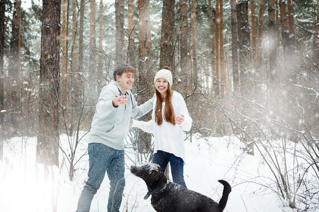 Young funny couple having fun in snowy forest