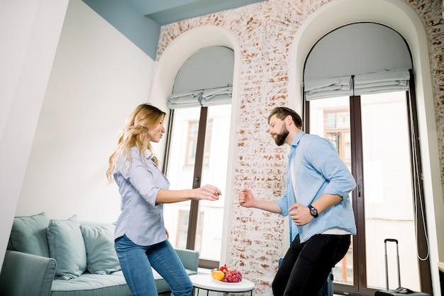 Молодая пара смешные в повседневной одежде, расслабляющий и танцевать вместе в гостиничном номере с красивыми окнами.