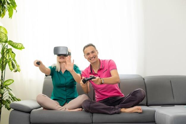 彼らのアパートでビデオゲームバーチャルリアリティグラスをプレイする若い面白いカップル-新しいトレンド技術を楽しんでいる幸せな人々-ゲームのコンセプト-女性のジョイパッドに焦点を当てる