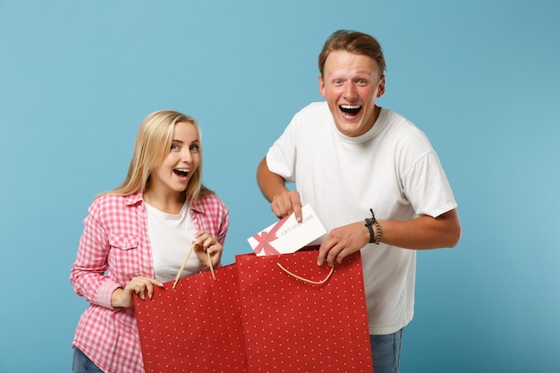 Young funny couple two friends guy and woman in white pink t-shirts posing