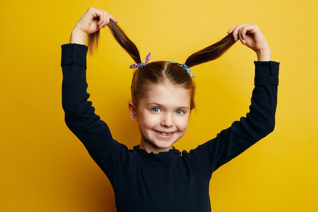 Молодая забавная милая маленькая девочка играет со своими волосами, хвостиками