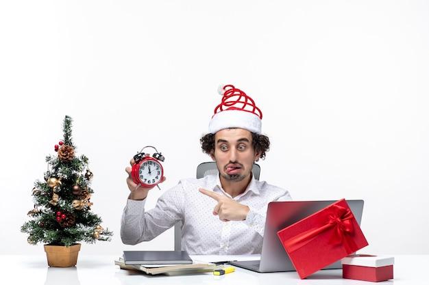 Молодой смешной эмоциональный взволнованный деловой человек в шляпе санта-клауса и указывающими часами сидит в офисе, высунув язык на белом фоне
