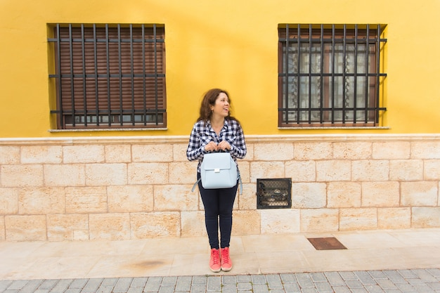 도시 배경에 포즈 핸드백과 젊은 재미 감정적 인 여자