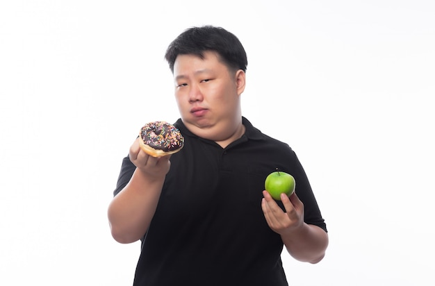 Young funny fat asian man choosing between chocolate donuts and green apple