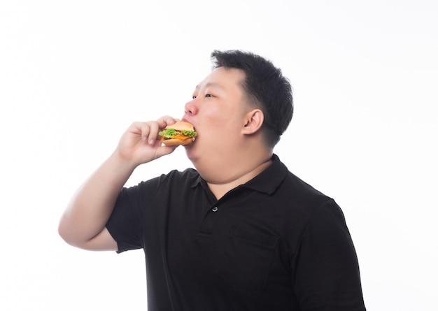 Молодой смешной толстый азиатский мужчина ест гамбургер