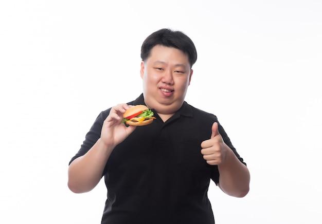 Молодой смешной толстый азиатский мужчина держит гамбургер и показывает палец вверх