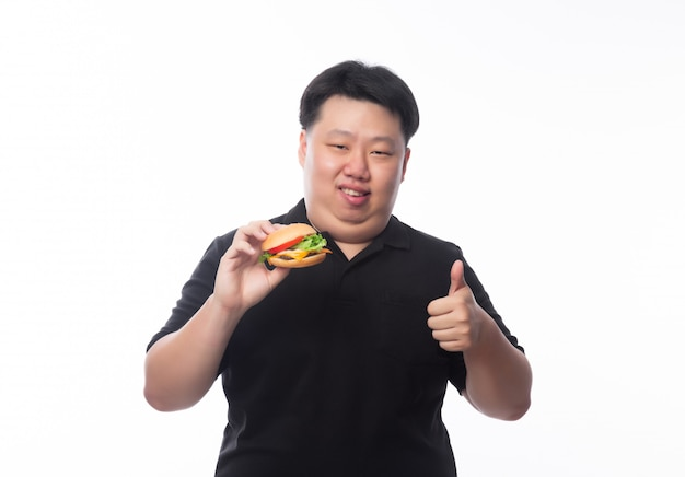 Young funny fat asian man holding hamburger and showing thumbs up