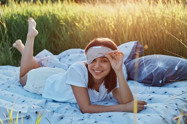 젊은 재미있는 여성 그녀의 수면 마스크를 제기 하 고 행복 한 표정으로 카메라를보고 웃 고, 여자는 일몰에 초원에서 부드러운 침대에 누워.