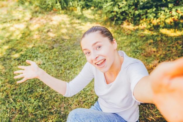 面白い少女は、緑の芝生の公園や庭の背景の上に座って携帯電話で手からselfieを取る。夏の日にスマートフォンでselfie写真を作る若い魅力的な女性の肖像画。