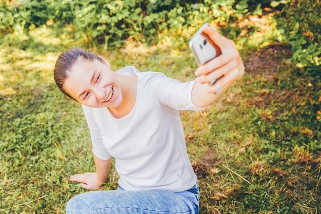 面白い少女は、緑の芝生の公園や庭に座って携帯電話で手からselfieを取る。夏の日にスマートフォンでselfie写真を作る若い魅力的な女性の肖像画。