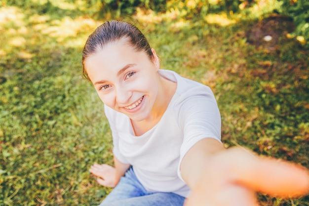 面白い少女は、緑の芝生公園や庭に座って携帯電話で手からselfieを取る。夏の日にスマートフォンでselfie写真を作る若い魅力的な女性の肖像画。