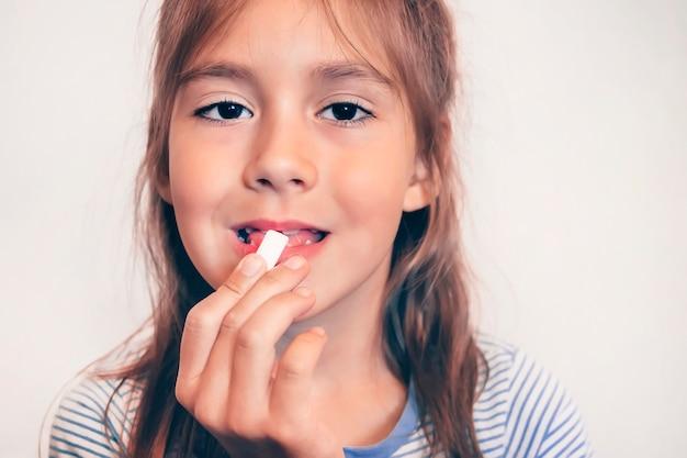껌을 씹는 재미 있는 어린 소녀. 신선한 숨. 구취. 껌으로 식사 후 양치질하기. 아이는 흰색 쿠션 껌 근접 촬영에 그의 열린 입을 넣습니다. 닦다.