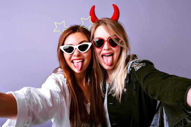 Молодые веселые девушки делают селфи, винтажные очки, повязки для волос на вечеринку дьявола и звезд, повседневную молодежную одежду, позитивное настроение.
