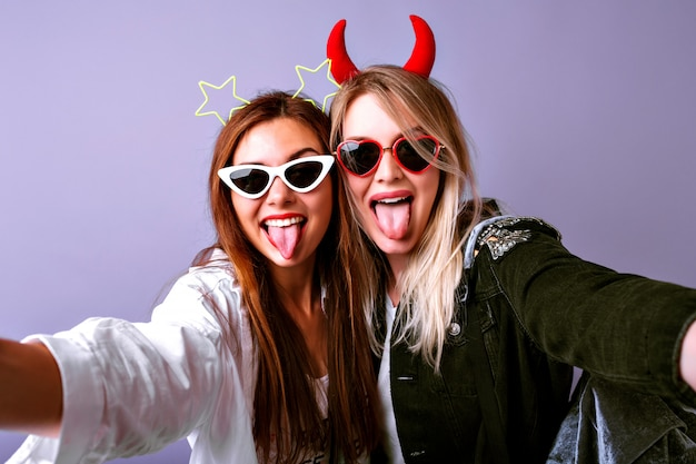 Young funny girls making selfie, vintage glasses, devil and stars party hair bands, casual youth clothes, positive mood.