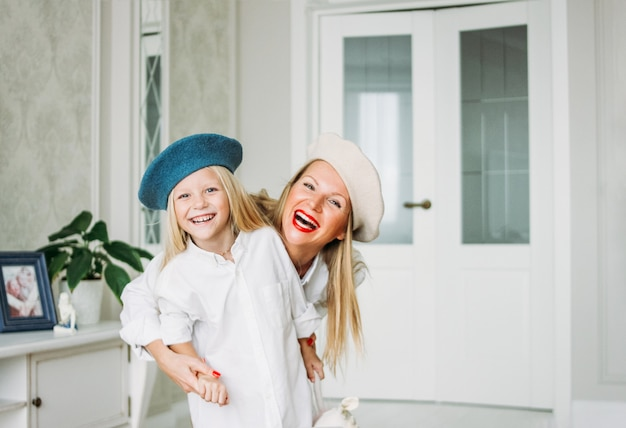 Young funny happy fair long hair mom and her cute daughter having fun together at living room, happy family lifestyle