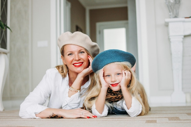 Young funny happy fair long hair mom and her cute girl dressed fashion family look having fun together lying on floor at living room, happy lifestyle
