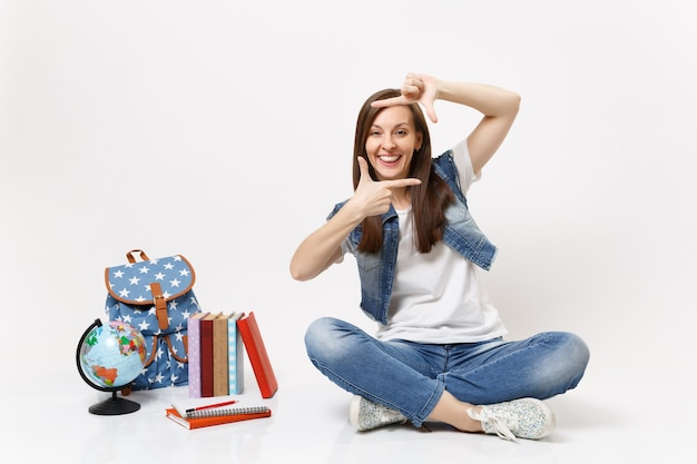Young funny happy woman student in denim clothes making hands photo frame gesture, sitting near globe, backpack, school books isolated on white wall
