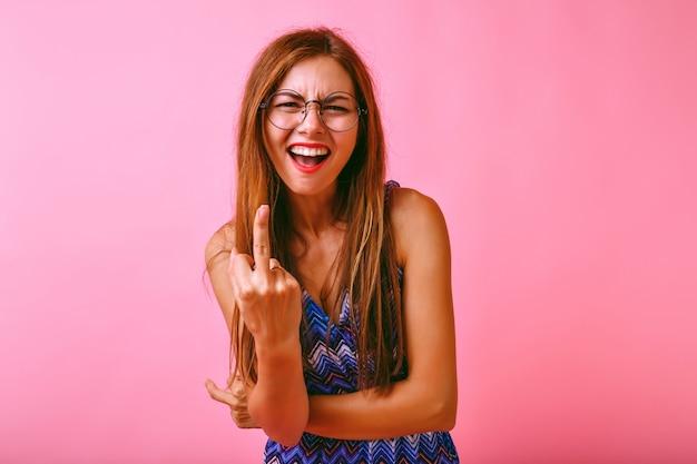 2つの中指を示す若い面白い流行に敏感な女性、彼女はあなた、積極的な概念に怒っています。